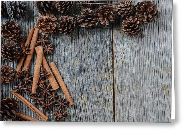 Pine Cones Greeting Cards - Cinnamon sticks star anise and pine cones on rustic wood Greeting Card by Brandon Bourdages