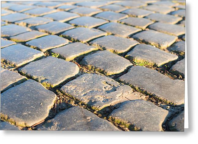 Old Roadway Greeting Cards - Closeup of a cobblestone road Greeting Card by Ruud Morijn