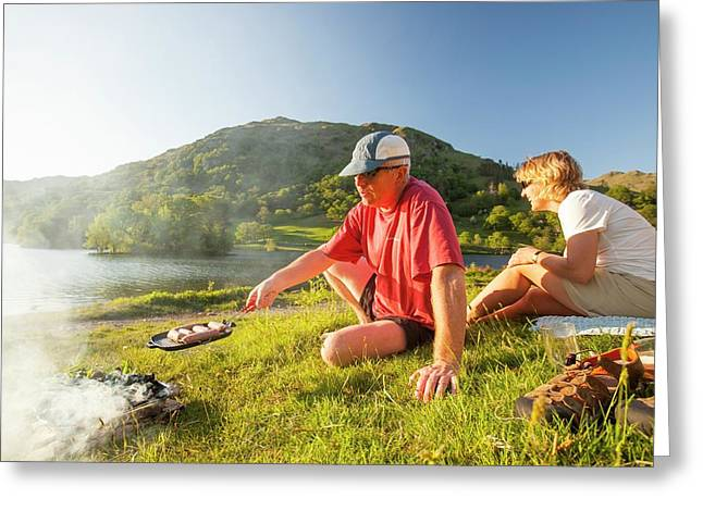 Couple Enjoying A Barbeque Greeting Card by Ashley Cooper