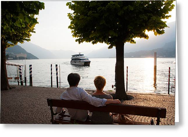 Bellagio Greeting Cards - Couple Sitting On Bench And Watching Greeting Card by Panoramic Images