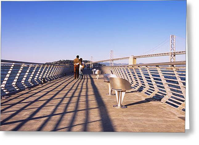 Casual Clothing Greeting Cards - Couple Walking On A Pier, Bay Bridge Greeting Card by Panoramic Images