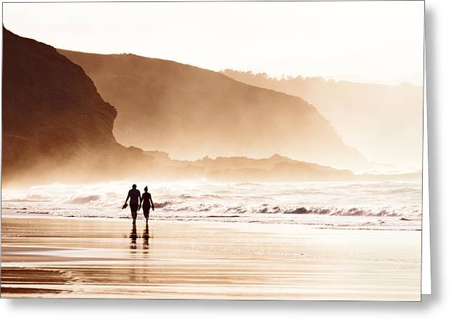 Foggy Beach Sunset Greeting Cards - Couple Walking On Beach With Fog Greeting Card by Mikel Martinez de Osaba