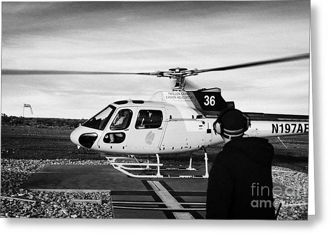 Helipad Greeting Cards - crew member watches papillon helicopter tour full of passengers take off from helipad at Grand canyo Greeting Card by Joe Fox