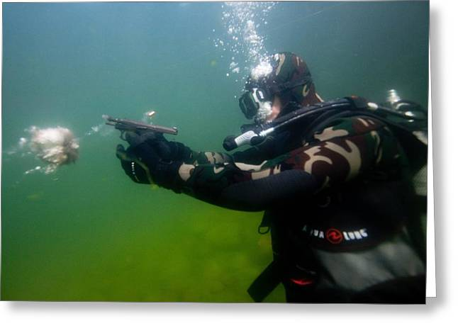 Discharging Greeting Cards - Diver firing a pistol underwater Greeting Card by Science Photo Library