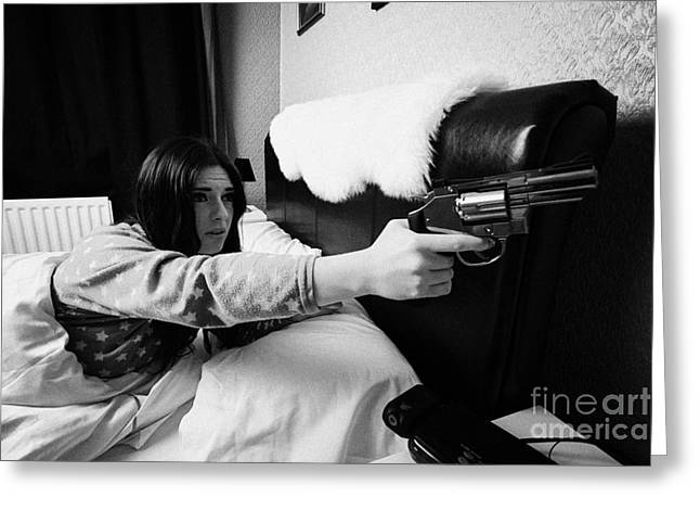 Bedside Table Greeting Cards - Early Twenties Woman Frightened Pointing Handgun Towards Door In Bed In A Bedroom Greeting Card by Joe Fox