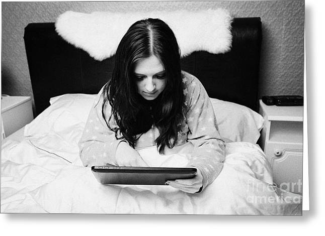 Web Surfing Greeting Cards - Early Twenties Woman Using Tablet Computer In Bed In A Bedroom Greeting Card by Joe Fox