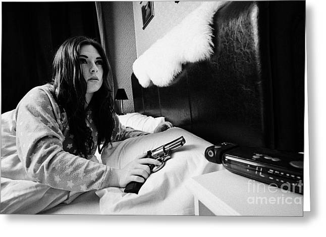 Bedside Table Greeting Cards - Early Twenties Woman Waking Holding Handgun In Bed In A Bedroom Greeting Card by Joe Fox