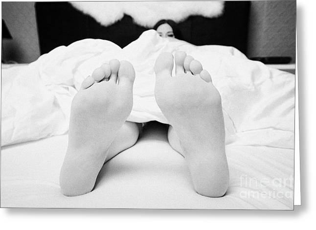 Sticking Out Greeting Cards - Early Twenties Woman With Feet Sticking Out Of Bottom Of Duvet In Bed In A Bedroom Greeting Card by Joe Fox