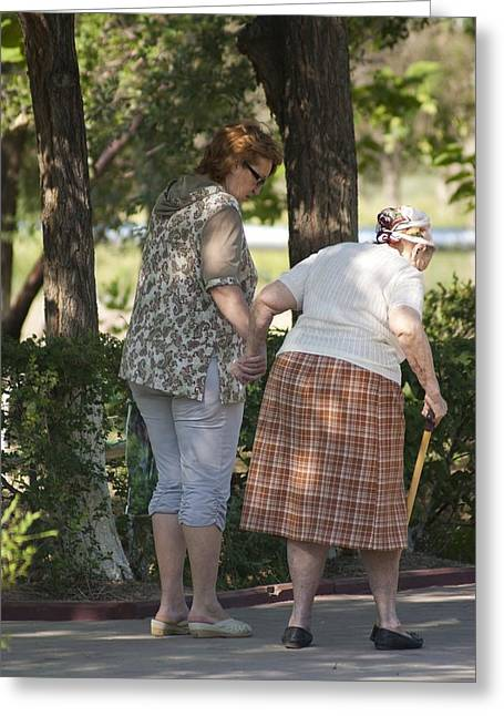 Cripple Greeting Cards - Elderly woman walking in a park Greeting Card by Science Photo Library