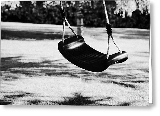 empty plastic swing swinging in a garden in the evening Greeting Card by Joe Fox