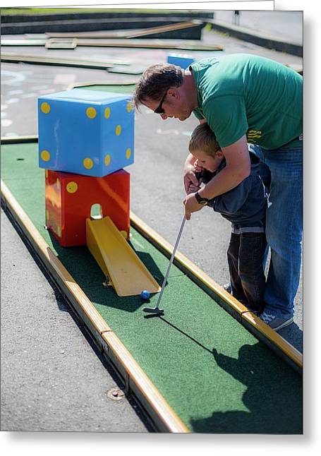Father Helping Son To Play Mini Golf Greeting Card by Samuel Ashfield