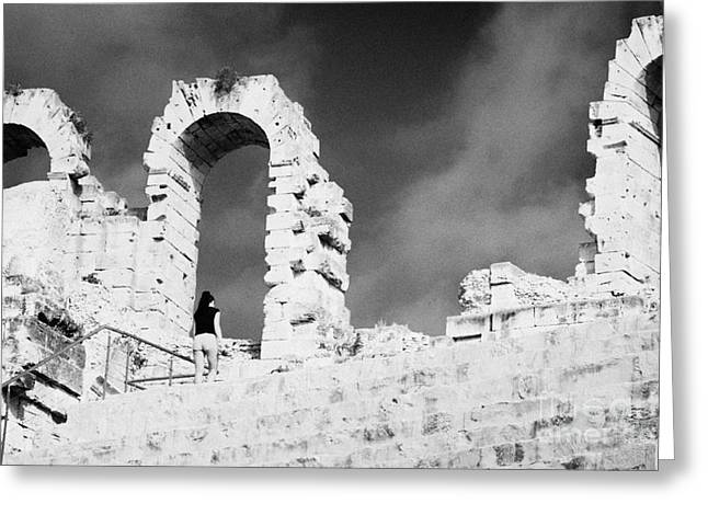 African Heritage Greeting Cards - Female Tourist Walks Up The Stepped Seating Area Towards Ruined Archways Of The Old Roman Colloseum At El Jem Tunisia Greeting Card by Joe Fox