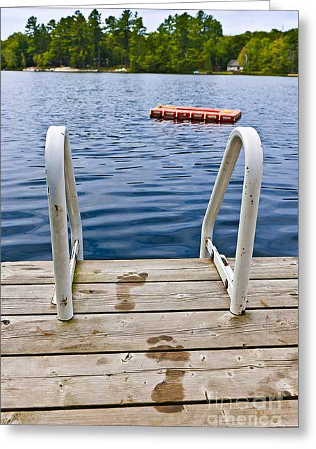 Print Photographs Greeting Cards - Footprints on dock at summer lake Greeting Card by Elena Elisseeva