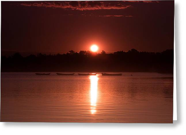Canoe Photographs Greeting Cards - Four boats in a row under a red sun rising Greeting Card by Chris Bordeleau