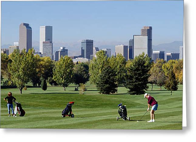 Four People Greeting Cards - Four People Playing Golf With Buildings Greeting Card by Panoramic Images