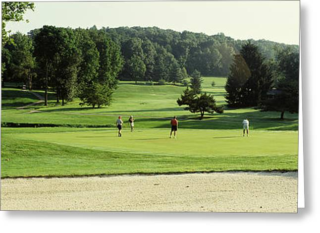 Four People Greeting Cards - Four People Playing On A Golf Course Greeting Card by Panoramic Images