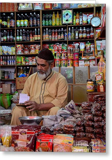 Owner Greeting Cards - General store keeper tends to paperwork at Empress Market Karachi Pakistan Greeting Card by Imran Ahmed