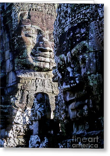 Ancient Ruins Greeting Cards - Gigantic face statues at Khmer temple Angkor Wat ruins Cambodi Greeting Card by Ryan Fox