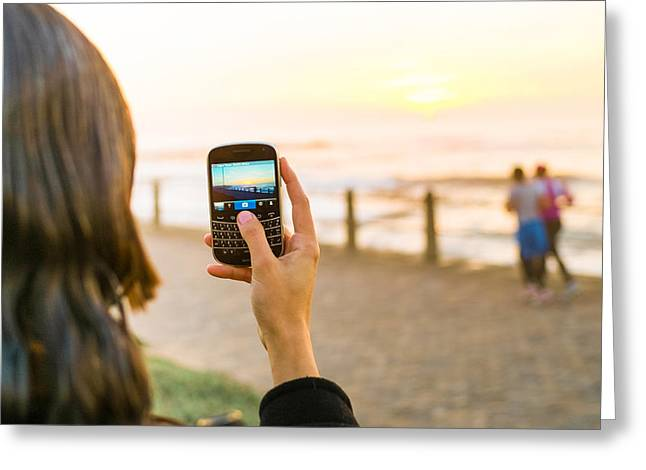 Cellphone Greeting Cards - Girl taking a picture of sunset at sea Greeting Card by John-james Gerber
