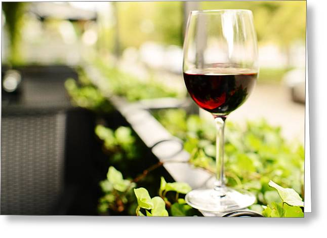 Wine Scene Greeting Cards - Glass of Red Wine in outdoor Cafe Greeting Card by Anna Bryukhanova