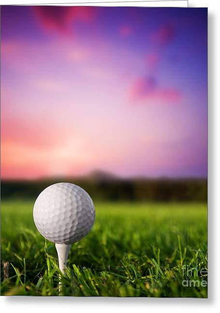Ball Games Greeting Cards - Golf ball on tee at sunset Greeting Card by Michal Bednarek