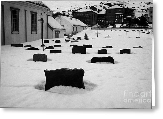 Headstones Greeting Cards - gravestones partially buried in the snow in the cemetery outside Honningsvag kirke church finnmark  Greeting Card by Joe Fox