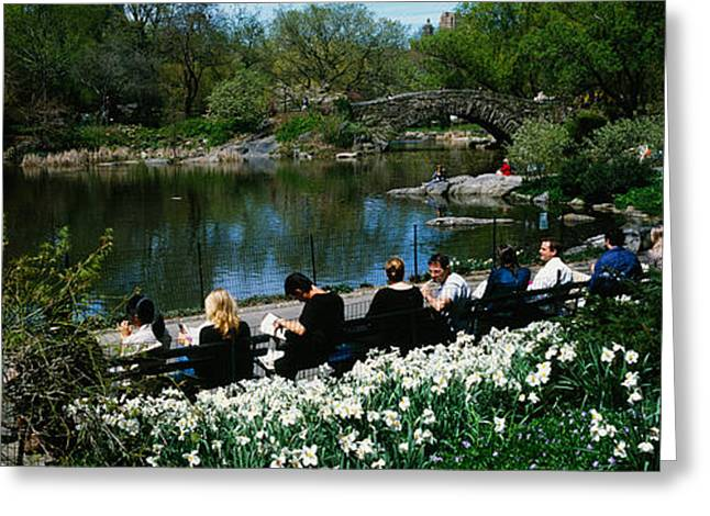 Reflection Of Trees In Water Greeting Cards - Group Of People Sitting On Benches Greeting Card by Panoramic Images