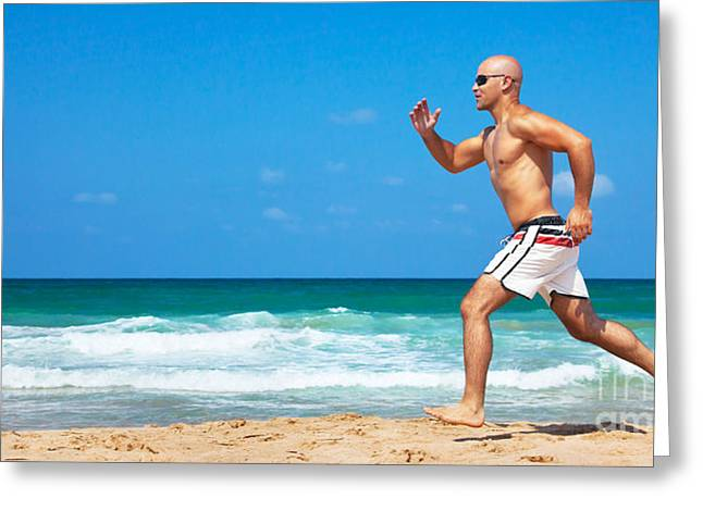Healthy man running on the beach Greeting Card by Anna Omelchenko