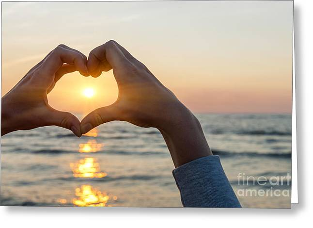 Beautiful Day Greeting Cards - Heart shaped hands framing ocean sunset Greeting Card by Elena Elisseeva