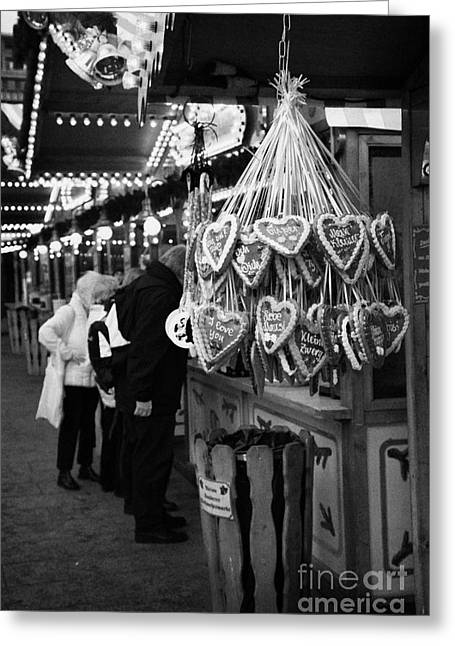 Berlin Germany Greeting Cards - heart shaped Lebkuchen hanging on a christmas market stall with tourists browsing in Berlin Germany Greeting Card by Joe Fox