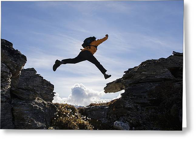 Knapsack Greeting Cards - Hiker Leaps Between Rocks Near Noatak Greeting Card by Scott Dickerson