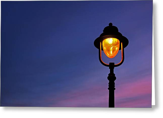 Evening Lights Greeting Cards - Lamppost Illuminated At Twilight Greeting Card by Mikel Martinez de Osaba