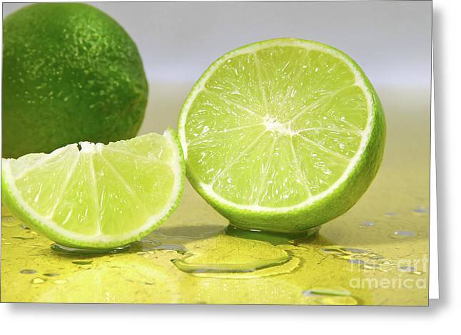 Limes On Yellow Surface Greeting Card by Sandra Cunningham
