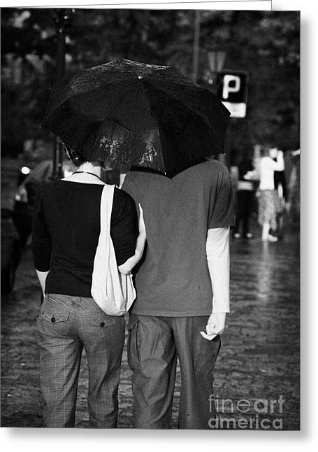Polish City Greeting Cards - Male And Female Couple Sharing An Umbrella Walking Arm In Arm Down A Wet Cobblestone Street In The Rain Krakow Greeting Card by Joe Fox