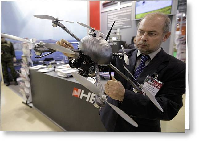 Hovering Greeting Cards - Man holding small UAV flying machine Greeting Card by Science Photo Library