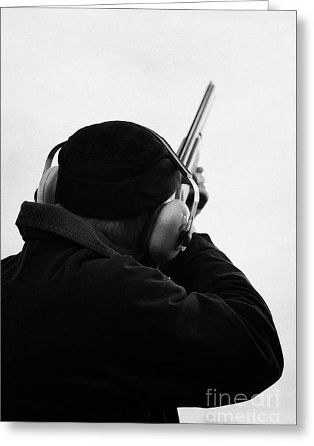 Man In Cap And Ear Defenders Takes Aim Into Sky With Shotgun On December Shooting Day Greeting Card by Joe Fox