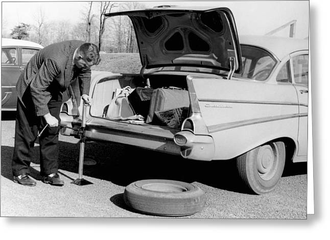Man Jacking Up A Car Greeting Card by Underwood Archives