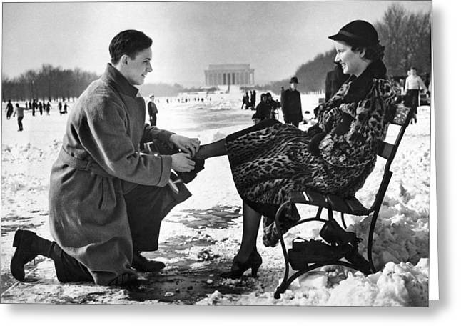 Man Lends A Helping Hand To Put On Skates Greeting Card by Underwood Archives