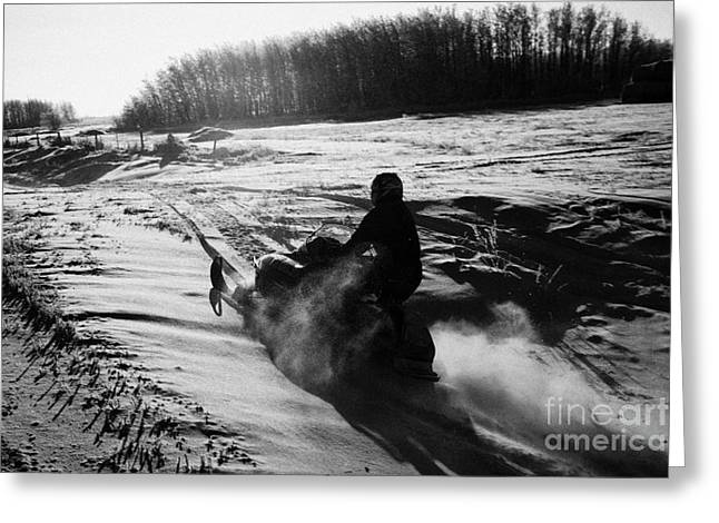 man on snowmobile crossing frozen fields in rural Forget canada Greeting Card by Joe Fox