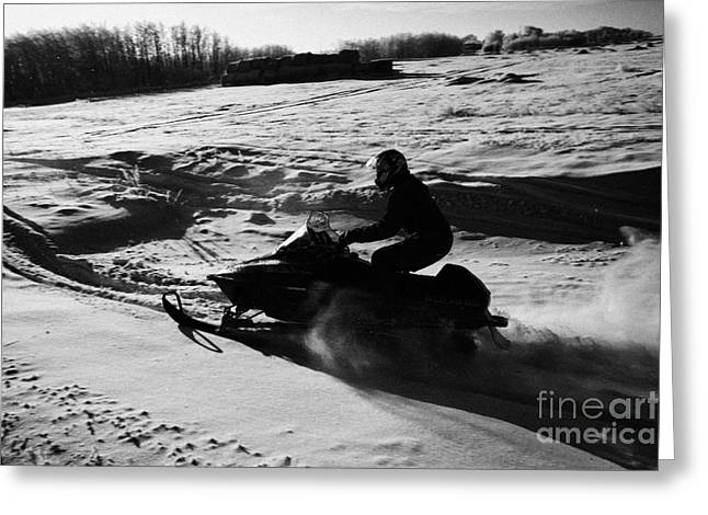 Harsh Conditions Greeting Cards - man on snowmobile crossing frozen fields in rural Forget Saskatchewan Greeting Card by Joe Fox