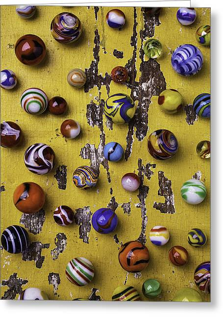 Amusements Greeting Cards - Marbles On Yellow Wooden Table Greeting Card by Garry Gay