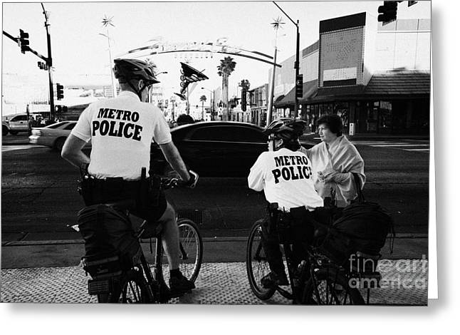Police Officer Greeting Cards - metro police bicycle cops help a tourist with directions in downtown Las Vegas Nevada USA Greeting Card by Joe Fox