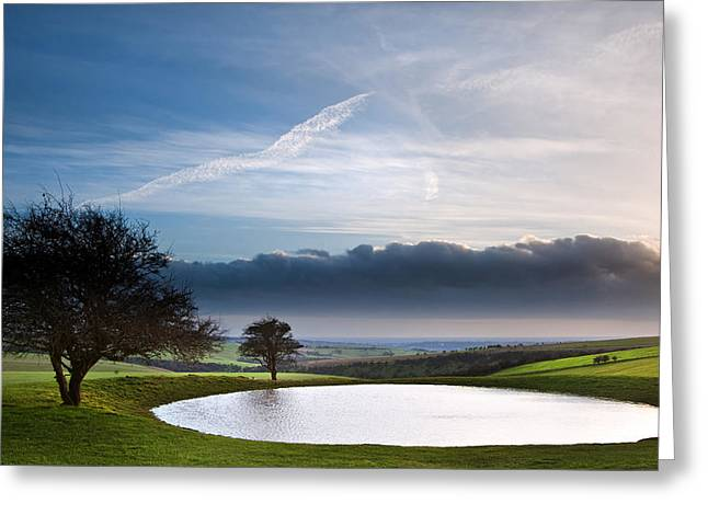 Naturally formed dew pond in countryside landscape with moody sk Greeting Card by Matthew Gibson