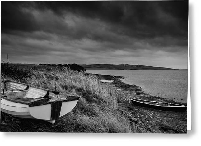 Stormy Weather Greeting Cards - Old decayed rowing boats on shore of lake with stormy sky overhe Greeting Card by Matthew Gibson