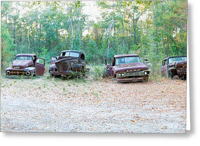 Antique Automobiles Greeting Cards - Old Rusty Cars And Trucks In A Field Greeting Card by Panoramic Images