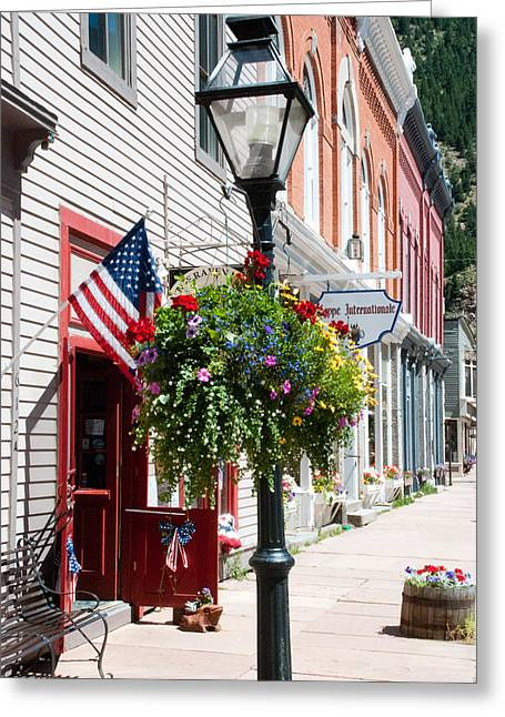 Geobob Greeting Cards - Old Street Lamp Flags and Flowers in Historic Georgetown Colorado Greeting Card by Robert Ford
