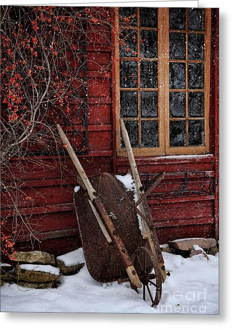 Atmosphere Greeting Cards - Old wheelbarrow leaning against barn in winter Greeting Card by Sandra Cunningham