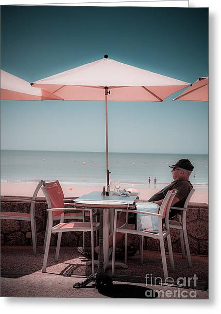 One Man Sitting Under Umbrella At Cafe Table By Beach. Greeting Card by Peter Noyce