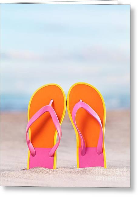 Beach Wear Greeting Cards - Pair of bright orange flip flops at the beach Greeting Card by Oleksiy Maksymenko