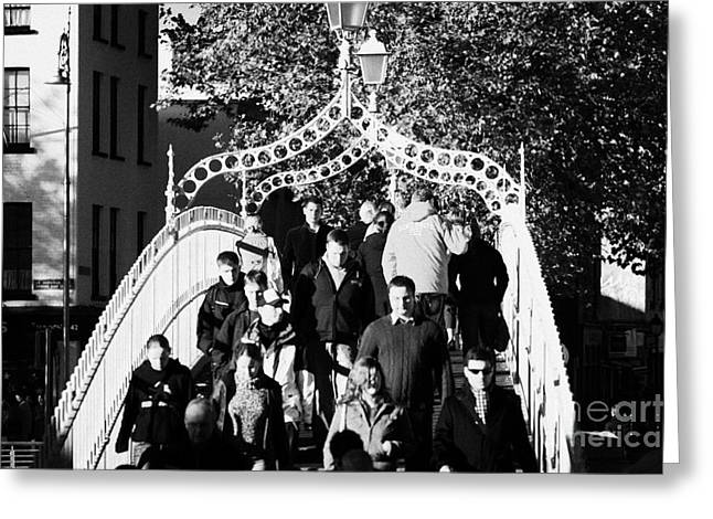 people crossing the hapenny ha penny bridge over the river liffey in dublin at a busy time Greeting Card by Joe Fox